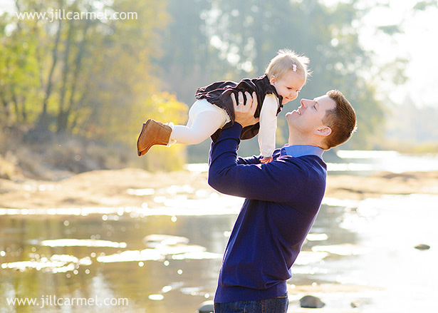 dad holds baby daughter in air with her brown ugg boots and corduroy dress