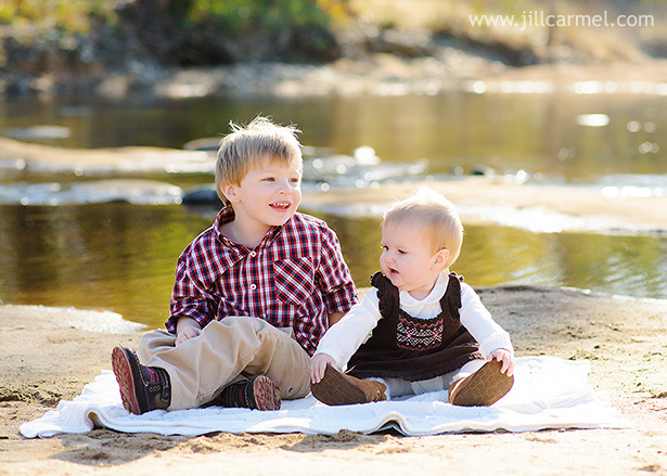 brother and sister sit together on a blanket at the river with water in the background