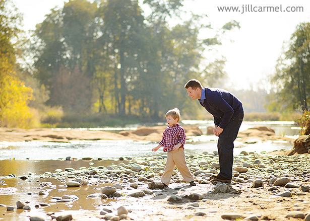 father and son throw rocks together at the river with trees and water in the background