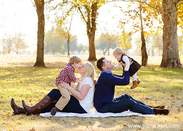mom and dad back to back with two kids laughing and kissing at the park with fall colors