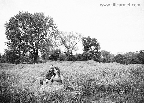 sitting together in sacramento grassy field for maternity portraits
