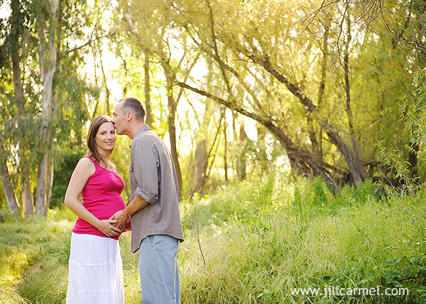 husband and wife together for maternity images by the river in sacramento surrounded by trees and grass