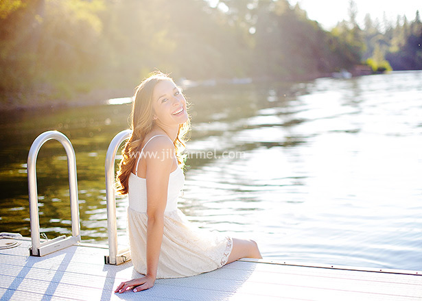 high school senior in Auburn sitting on the dock with the sun glowing behind her