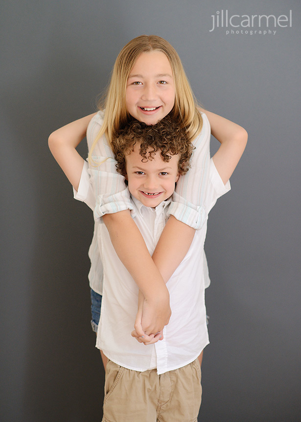 brother and sister hugs on gray studio backdrop