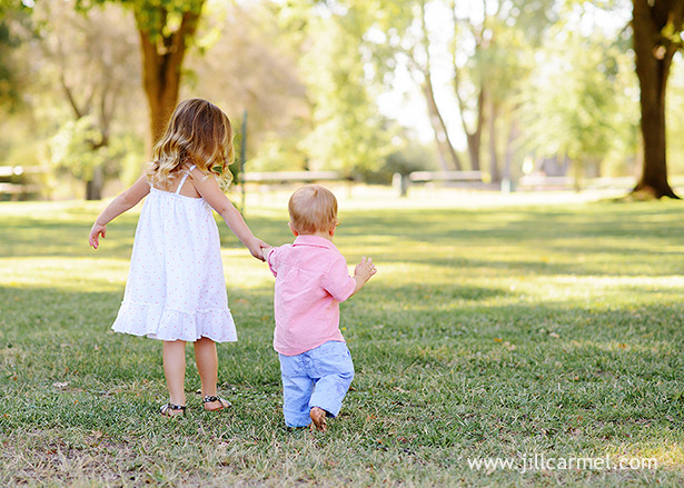 big sister holds her little brothers hand at the park
