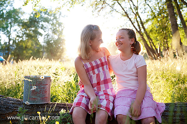 sisters laughing together in the sunset