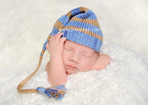 newborn baby doing a thinker pose with a blue elf hat