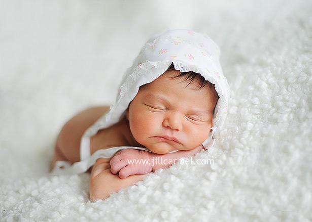 darling newborn baby with vintage cap