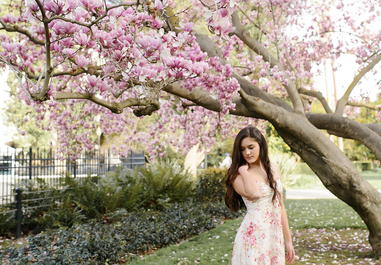 senior portraits under a pink magnolia tulip tree and floral dress