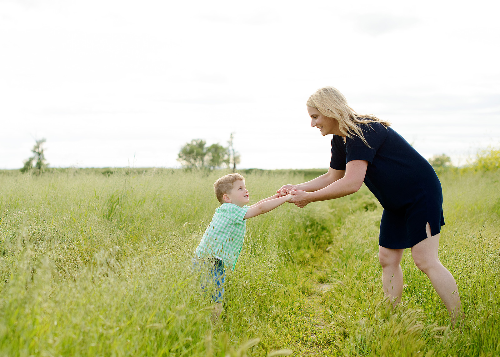 son dancing with his mother in the tall green grass for family picture day