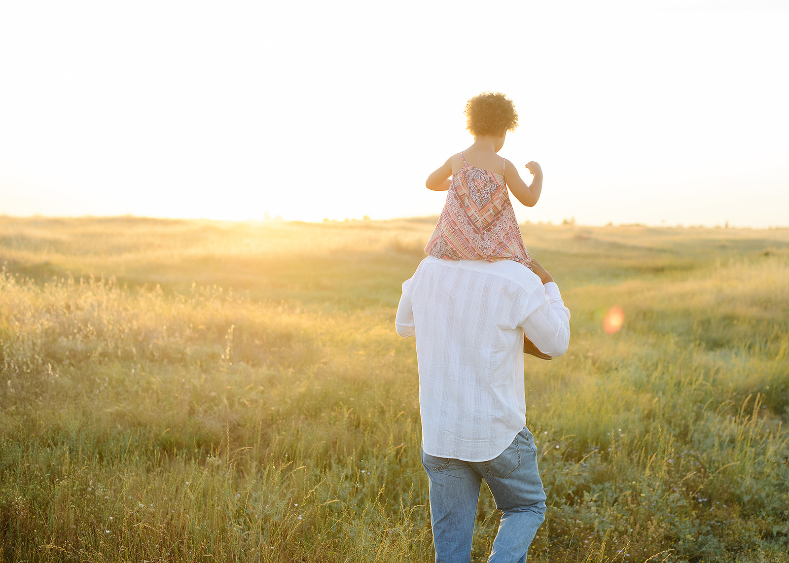 dad carrying daughter as the sun sets