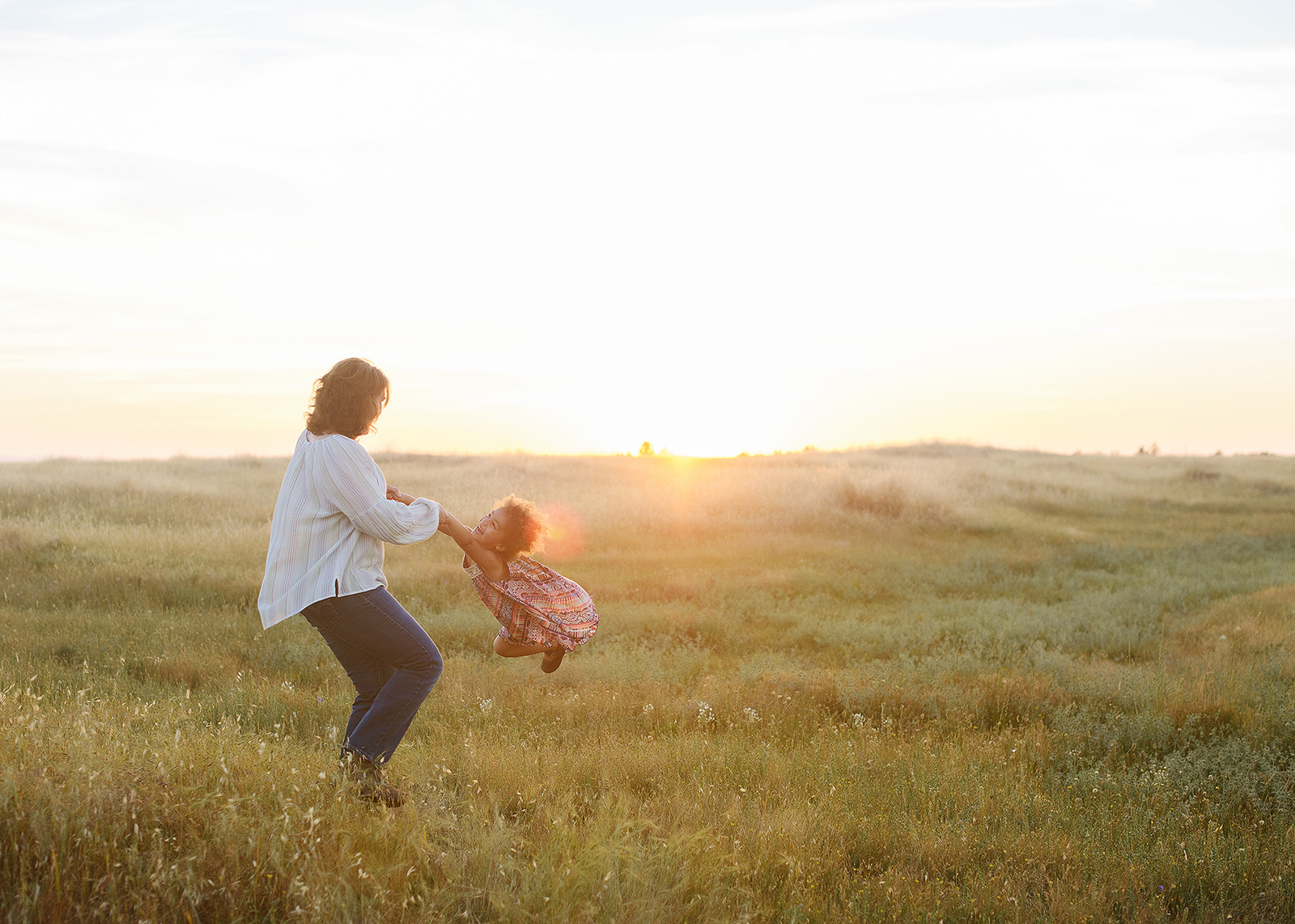 mother and daughter playing during sunset