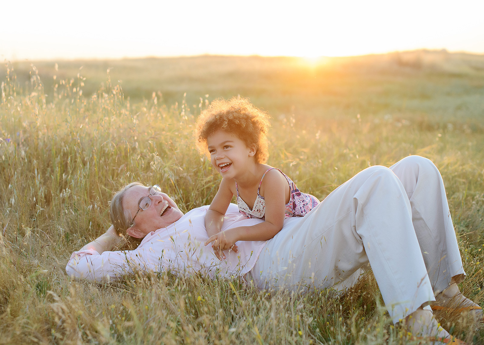 grandmother and granddaughter lying in the wildflower field