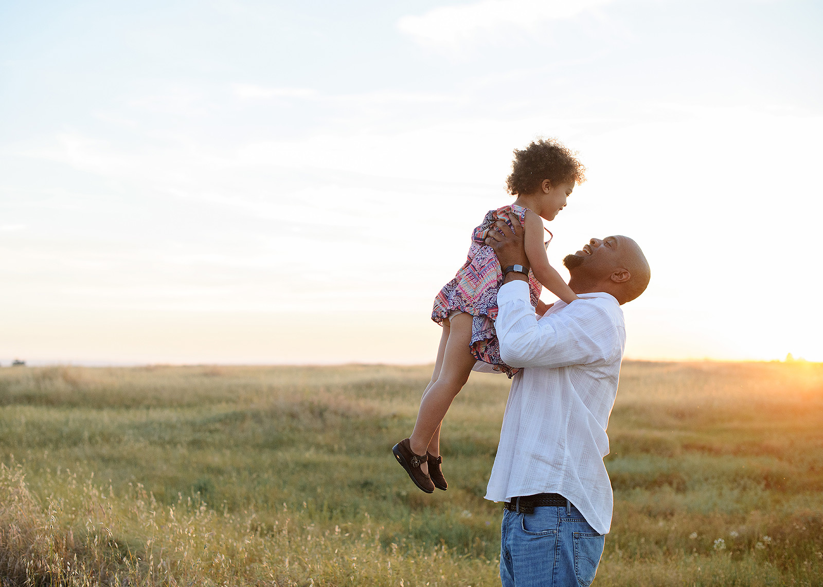 father playing with daughter in a field