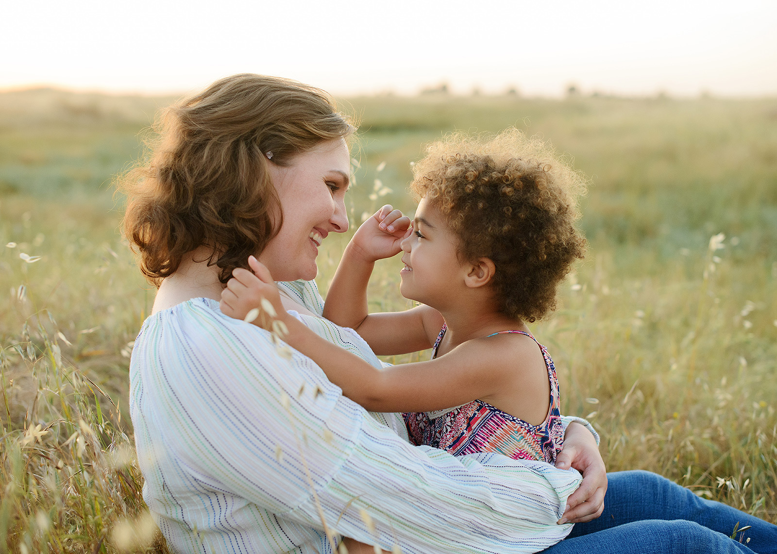 mother and daughter smiling in wildflower field