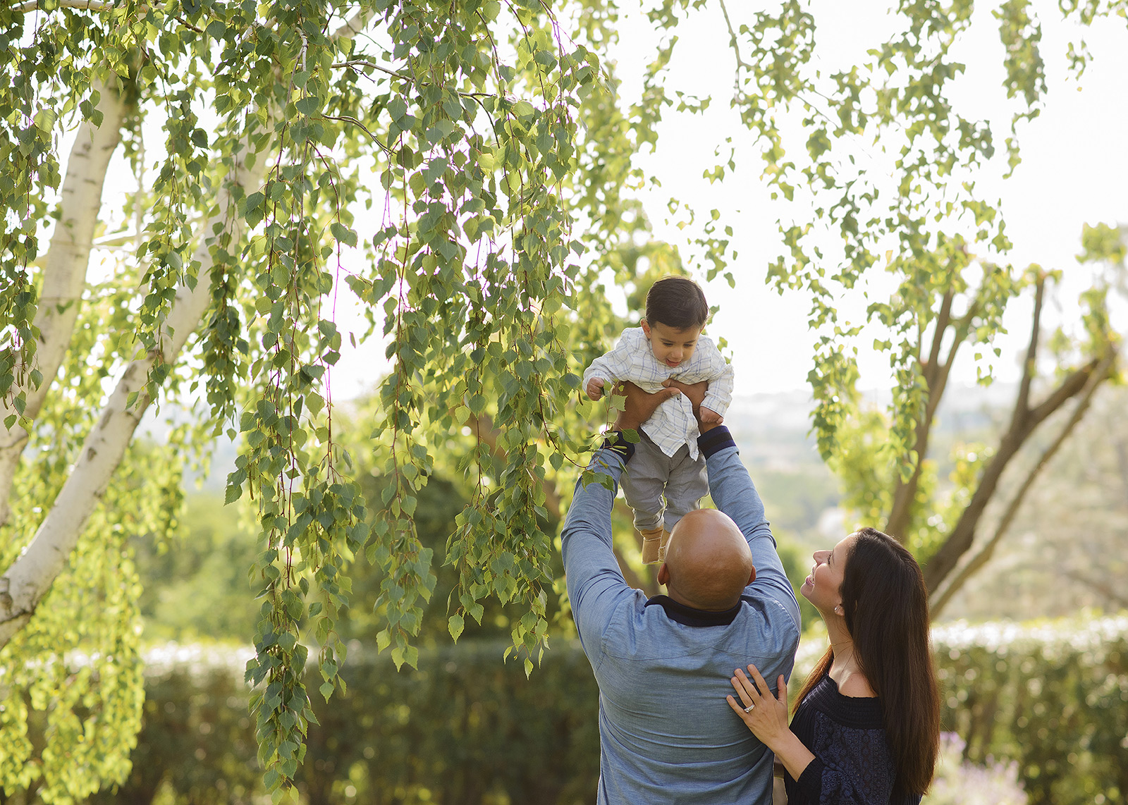 Mom, dad and baby boy playing outside with greenery and trees in a natural setting