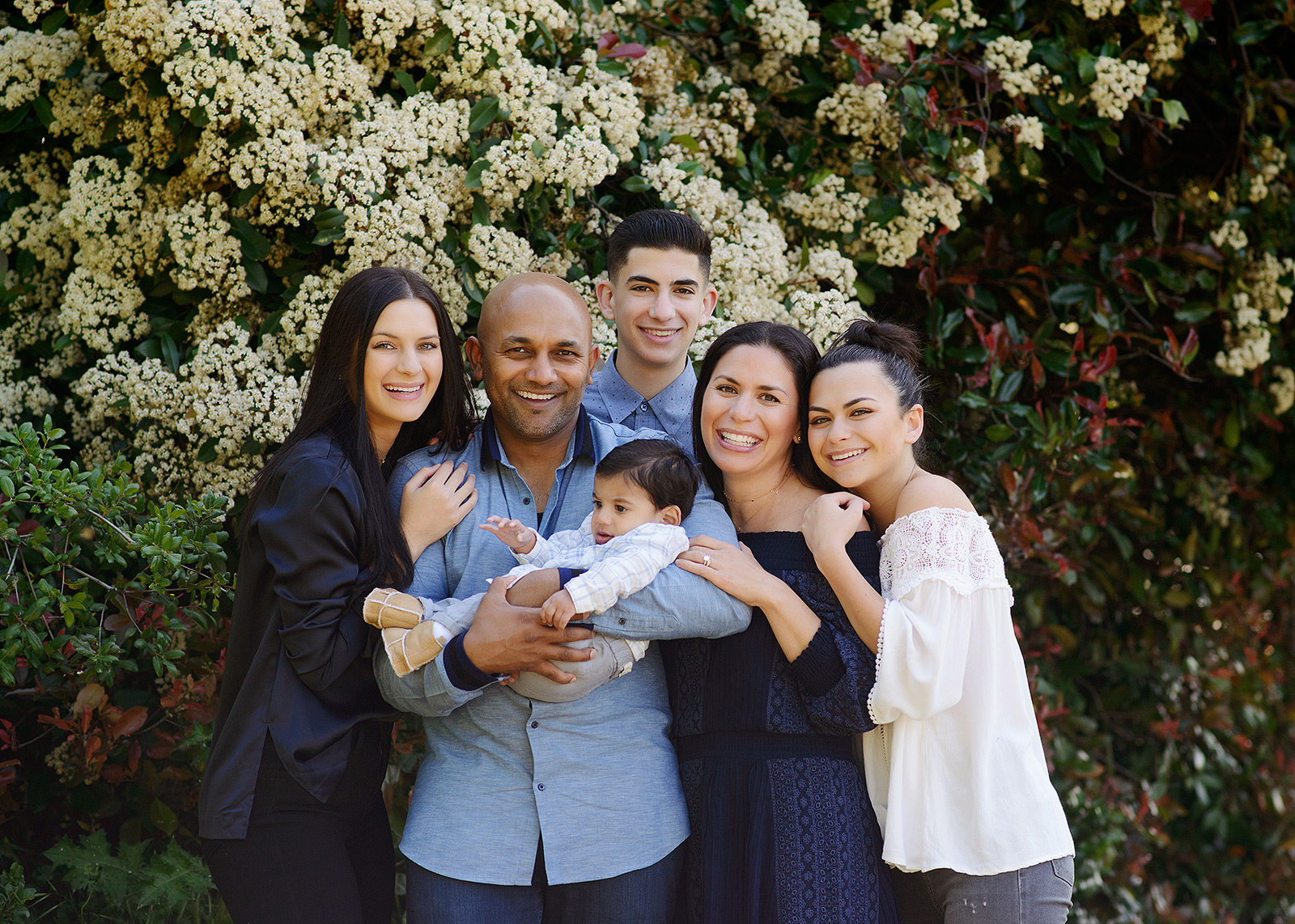 Family photos by flowering tree and a perfect example of portrait outfits and what to wear