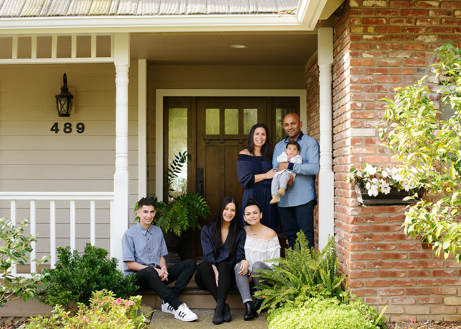 Family picture in front of door with a brick and wood background