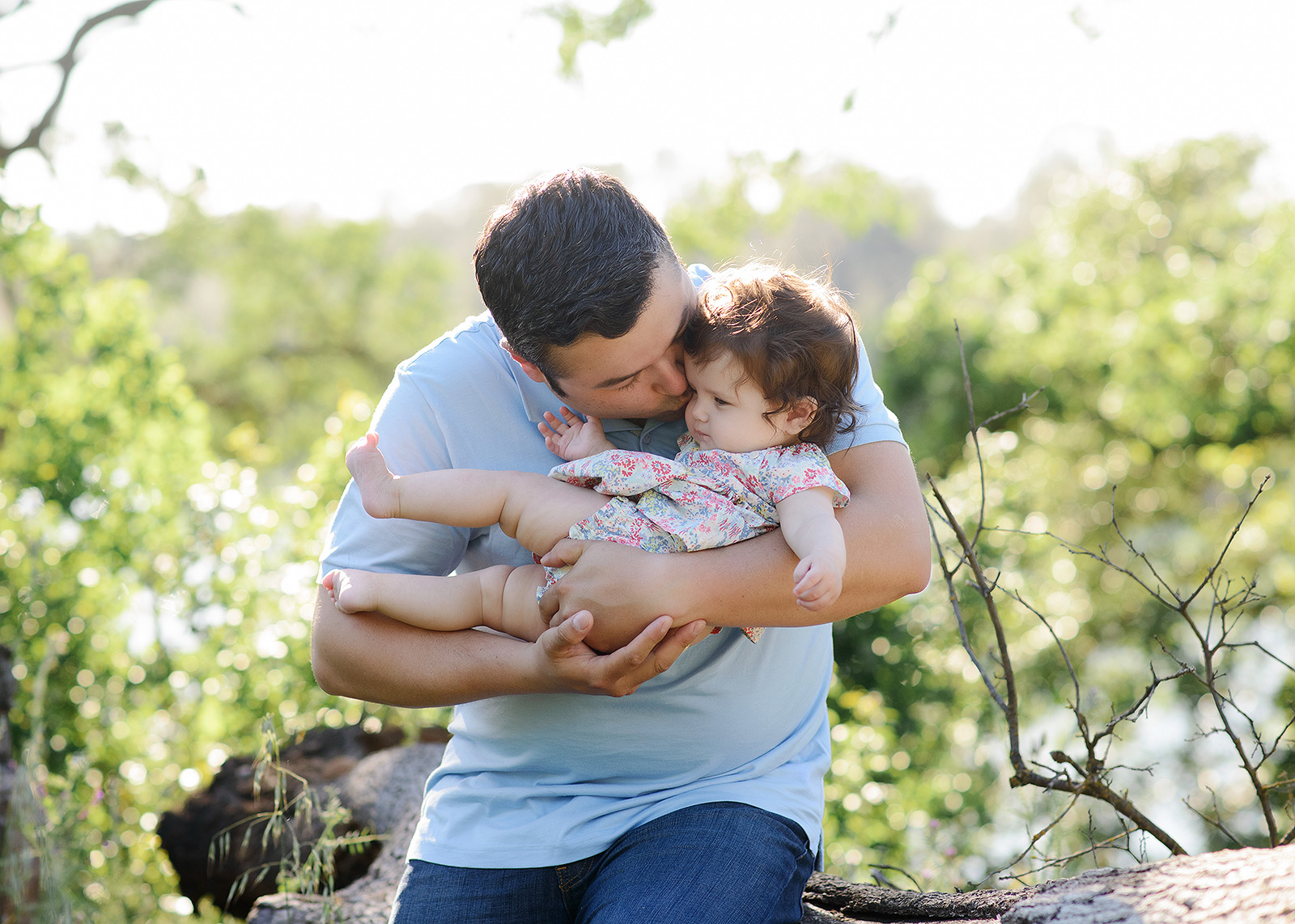 Dad kissing chubby baby on a log in natural light