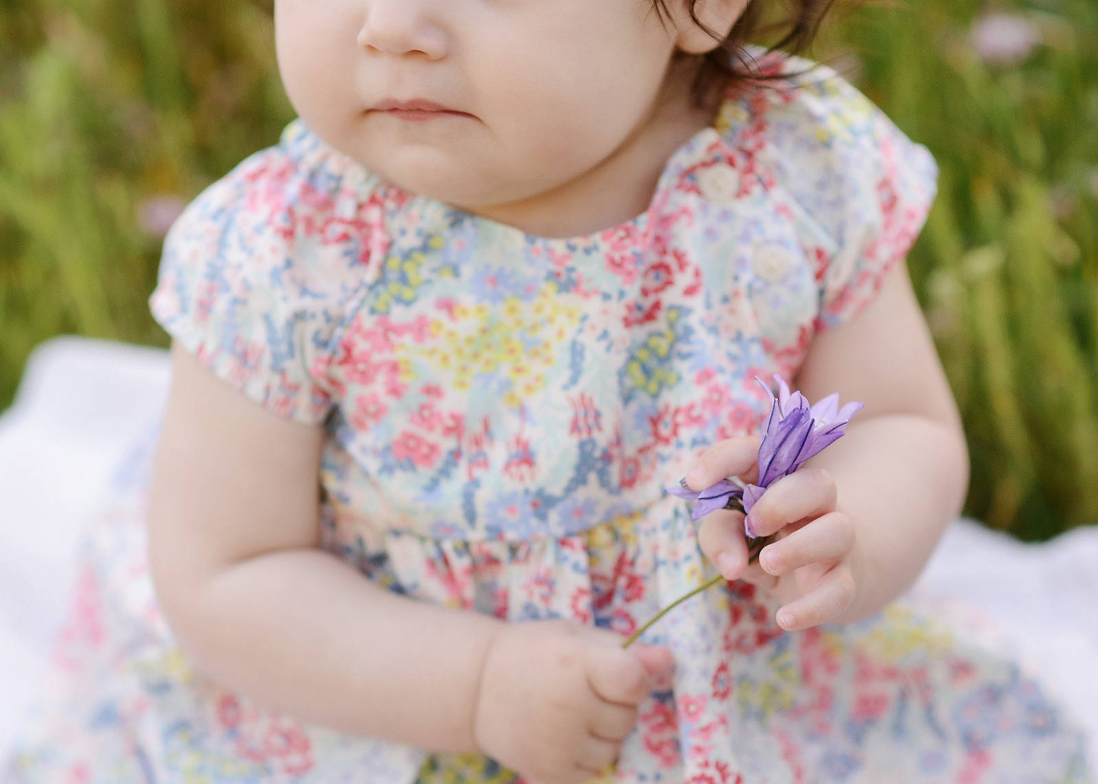 Baby in floral dress holding purple wildflower sitting in grass on a spring day in Folsom