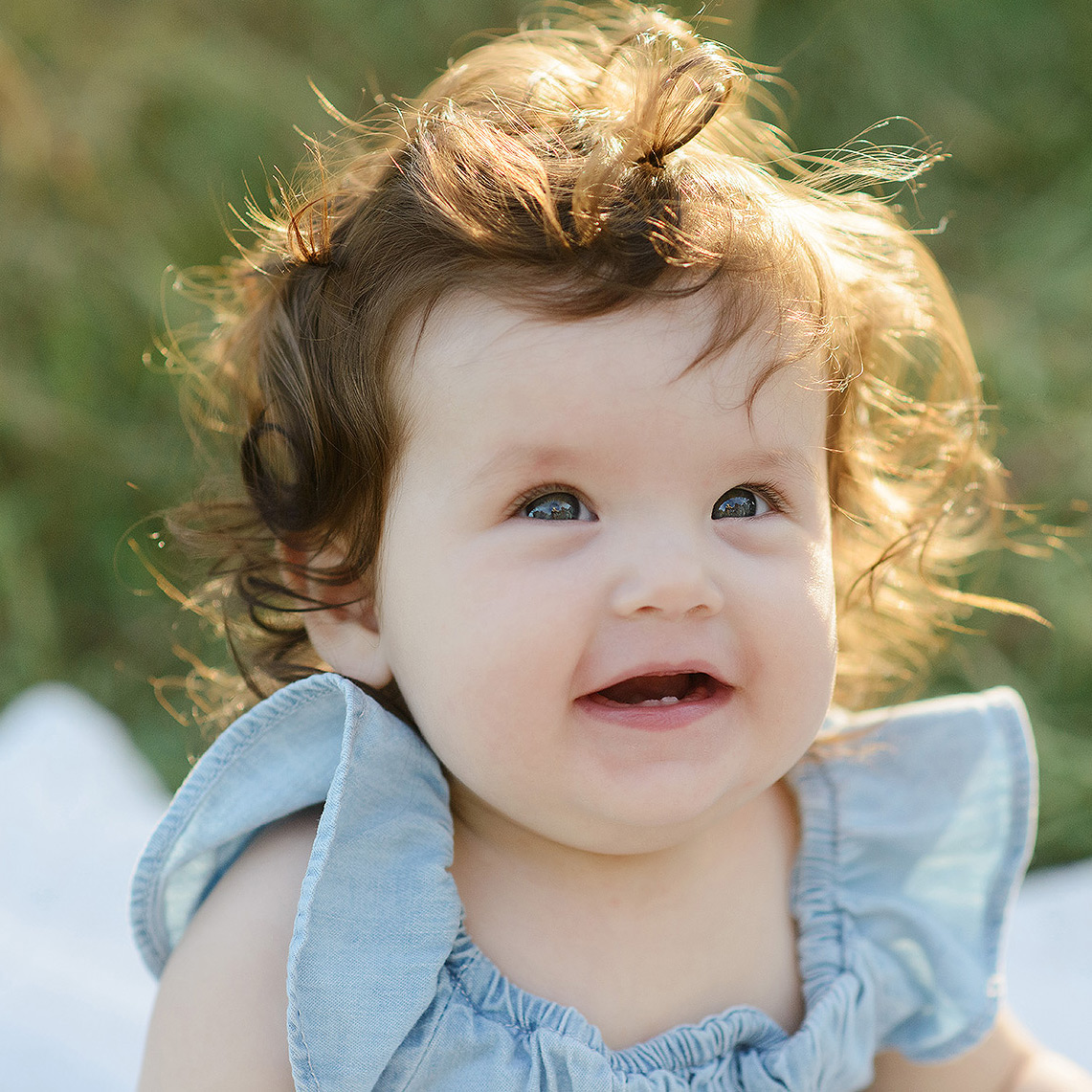 Smiling baby with curly hair in the sun