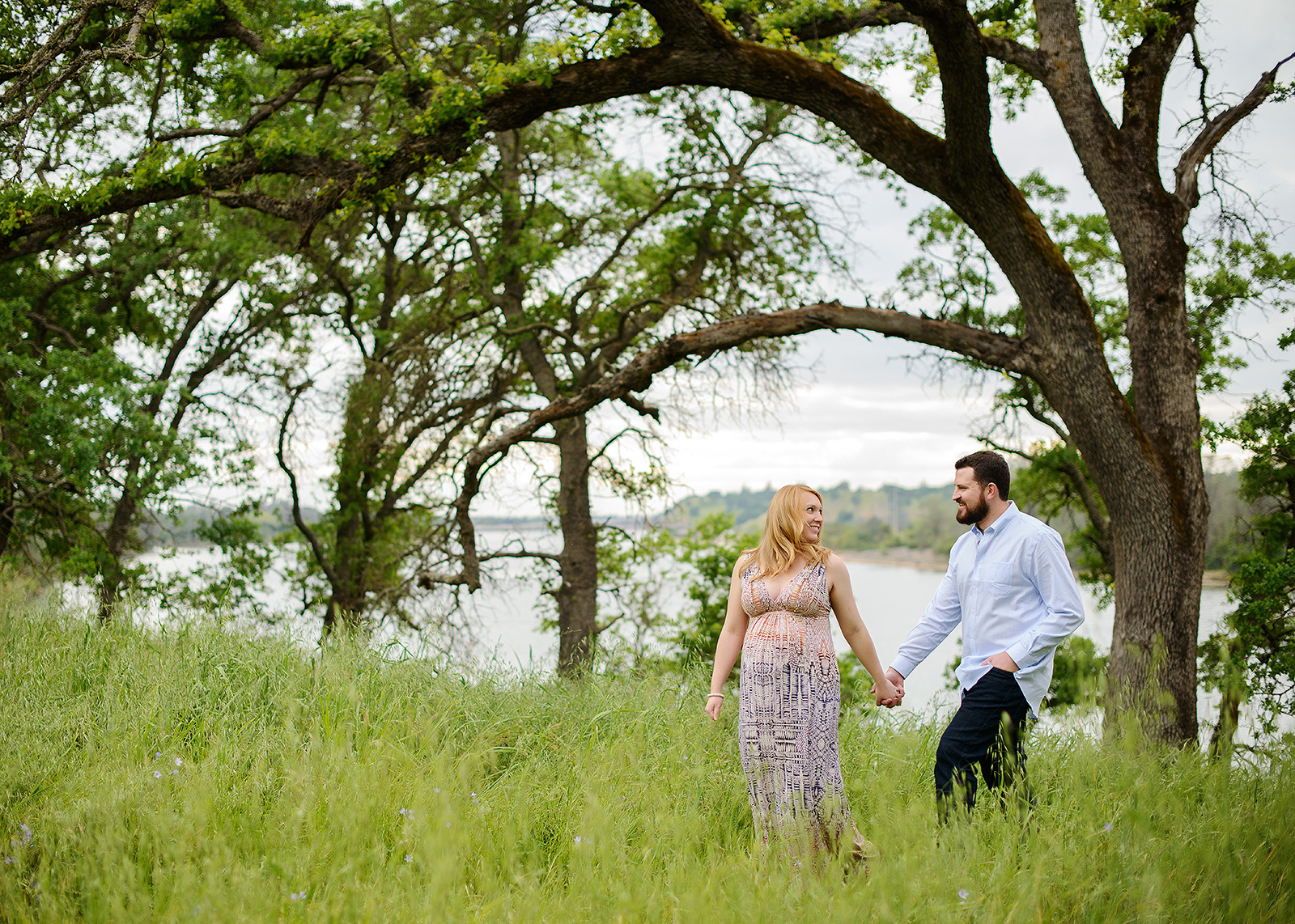 Expecting couple holding hands in tall grass with tree background, perfect for maternity portraits in folsom