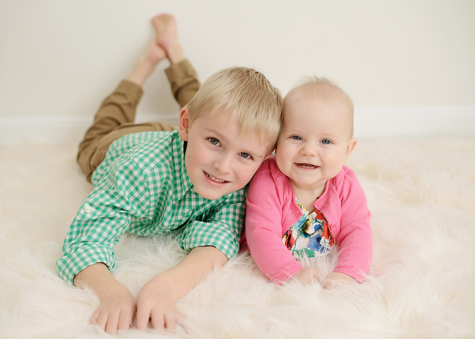 Big Brother and Baby Sister Smiling on Sheepskin Rug in Sacramento Studio