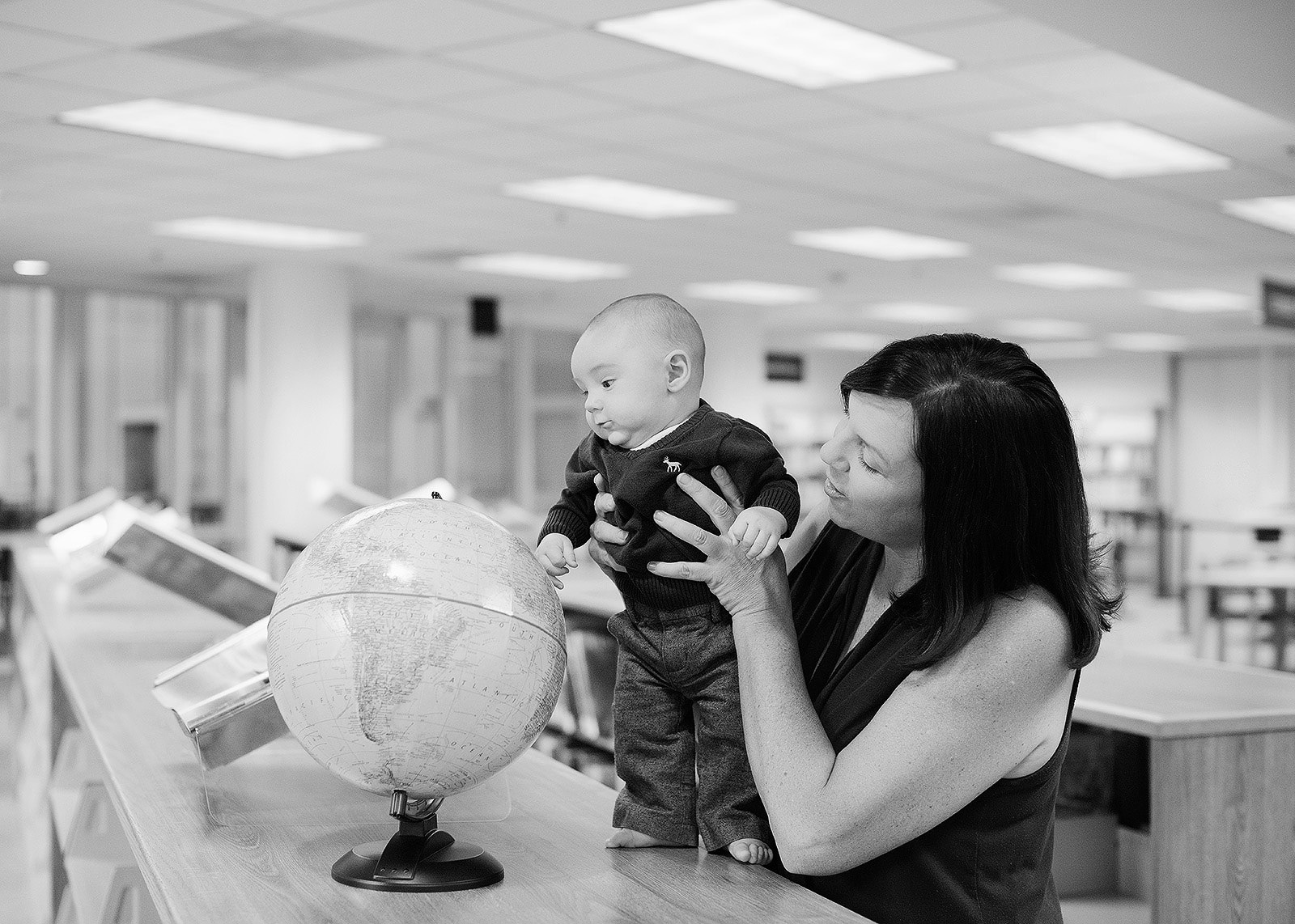 Baby Boy Looking at the World Globe with Mom Holding Him in Library