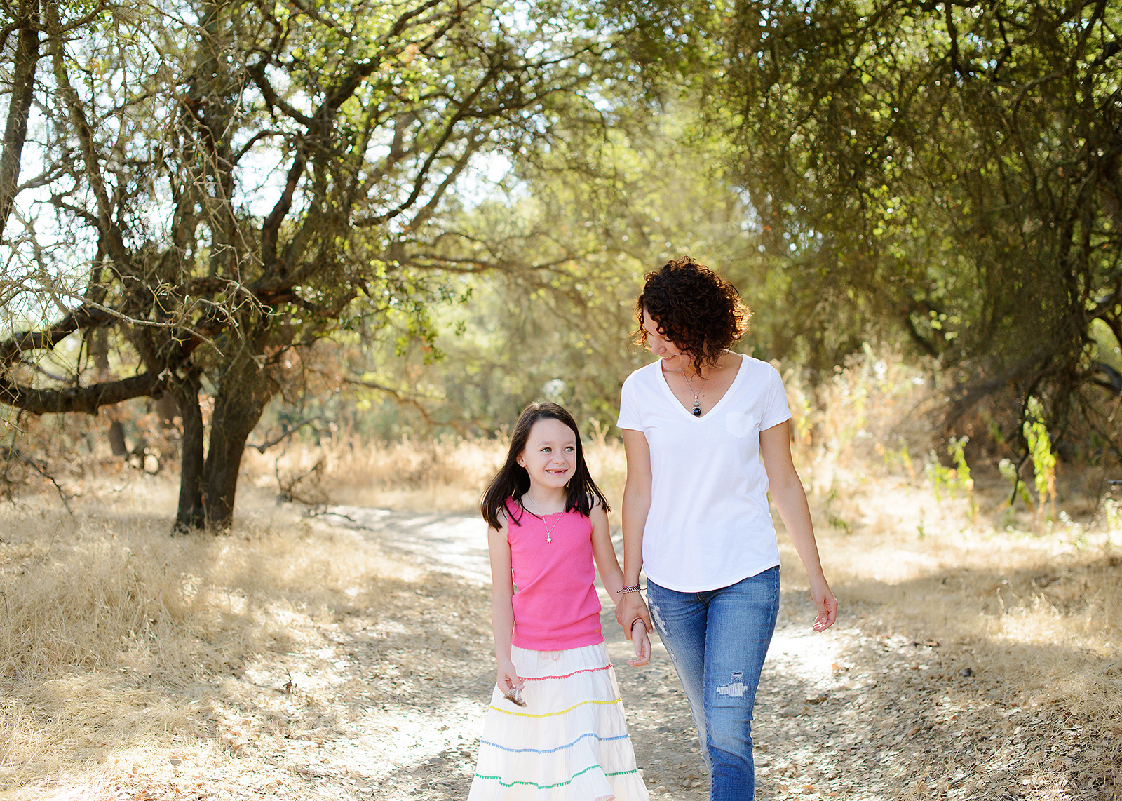 Mother and Daughter Walking in Nature Against Trees for family portraits at Effie Yeaw Nature Center