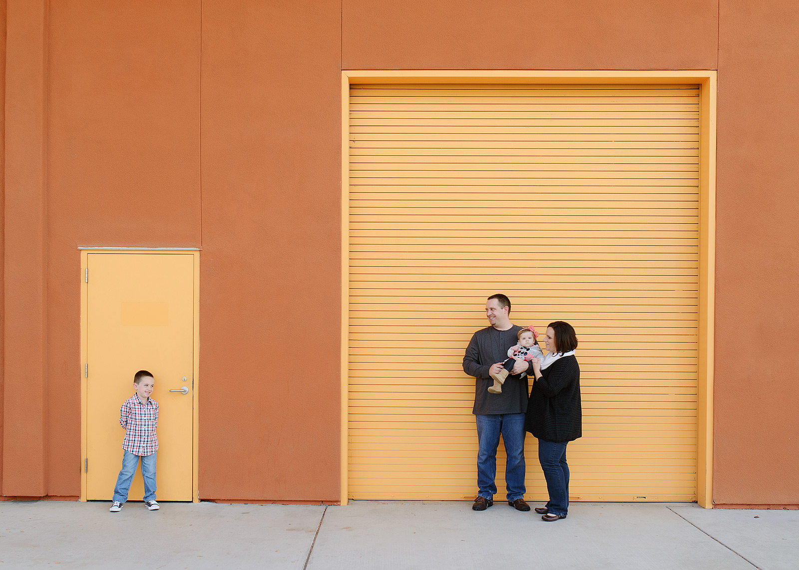 Family Photo Against Modern Industrial Orange Building in Rocklin