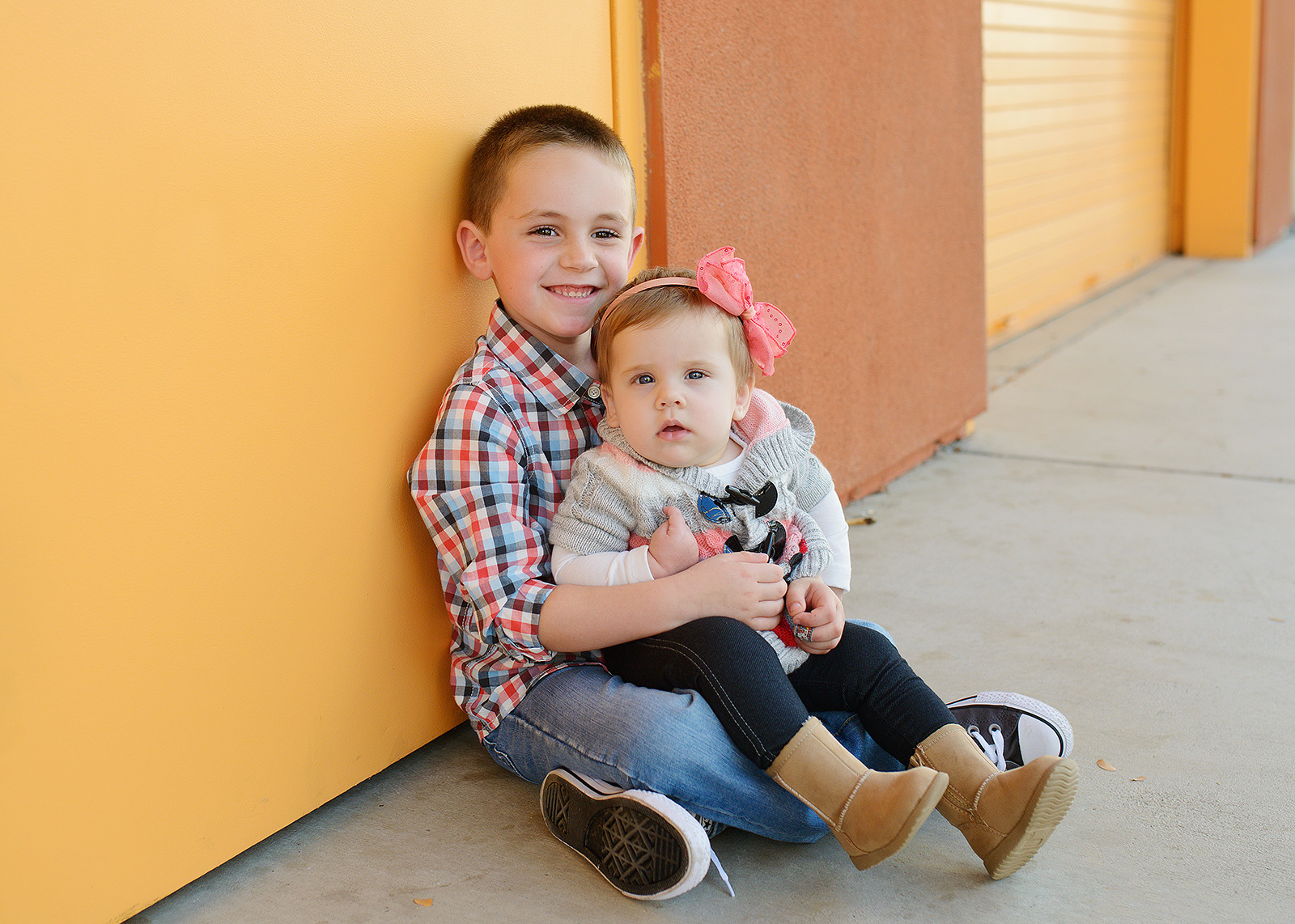 Brother and Baby Sister Leaning Against Bright Colorful Orange Building Rocklin Photographer
