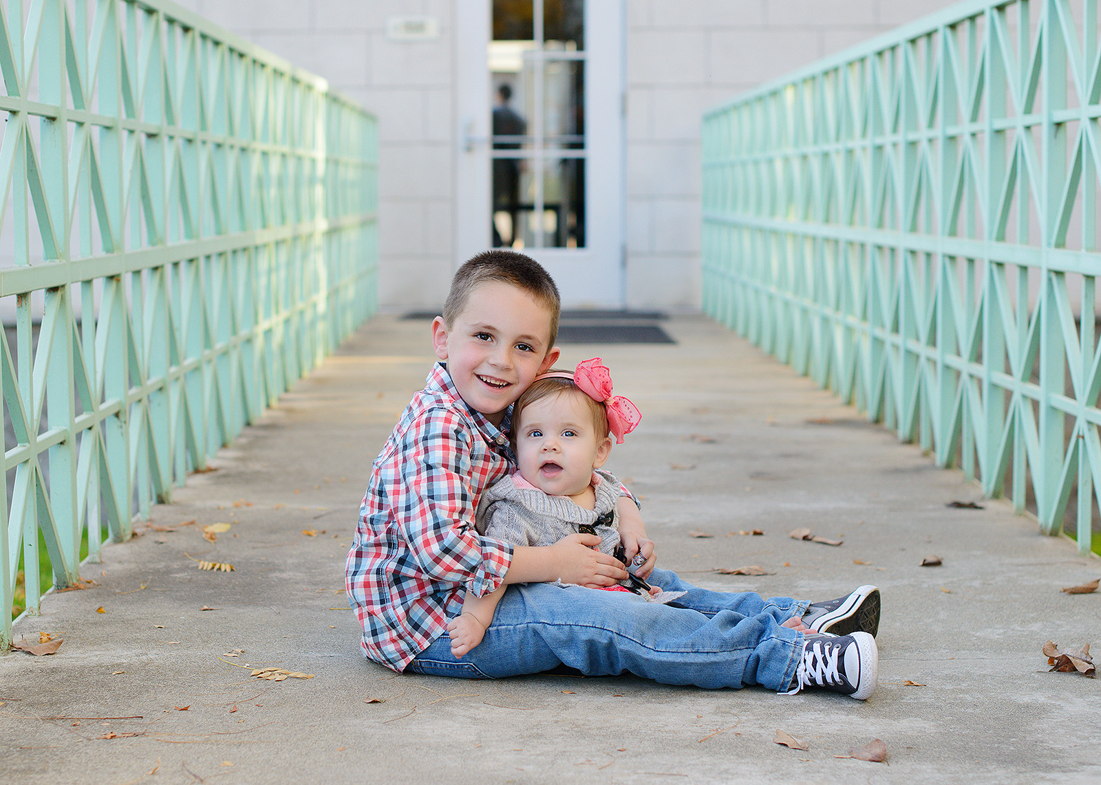 Brother and Baby Sister Hug in Between Green Rails in front of Modern Building Rocklin Photographer