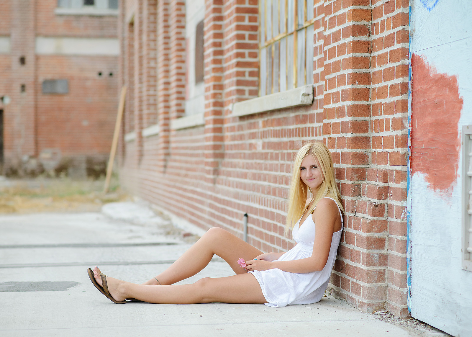 Senior Girl Sitting Against Red Brick Background in Old Sugar Mill in Clarksburg