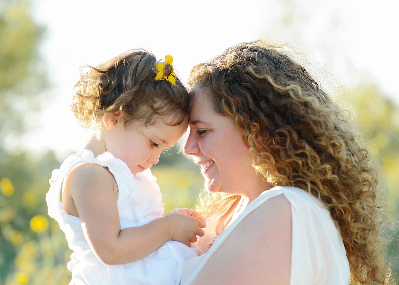 Mom and Daughter Smiling at Each Other in Natural Light with Wildflowers