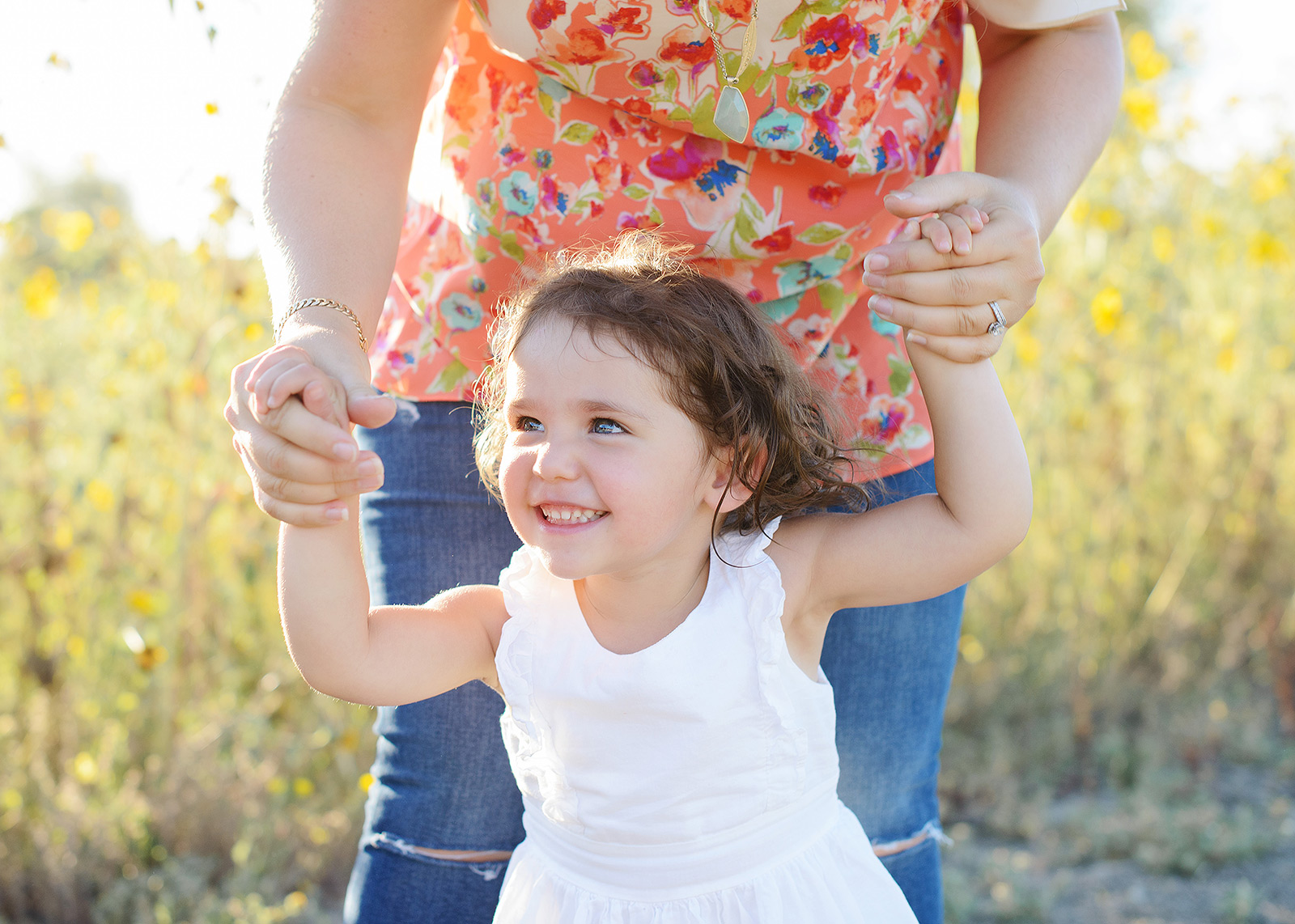 Daughter Laughing as Mom Holds Her to Walk with Yellow Wildflower Background