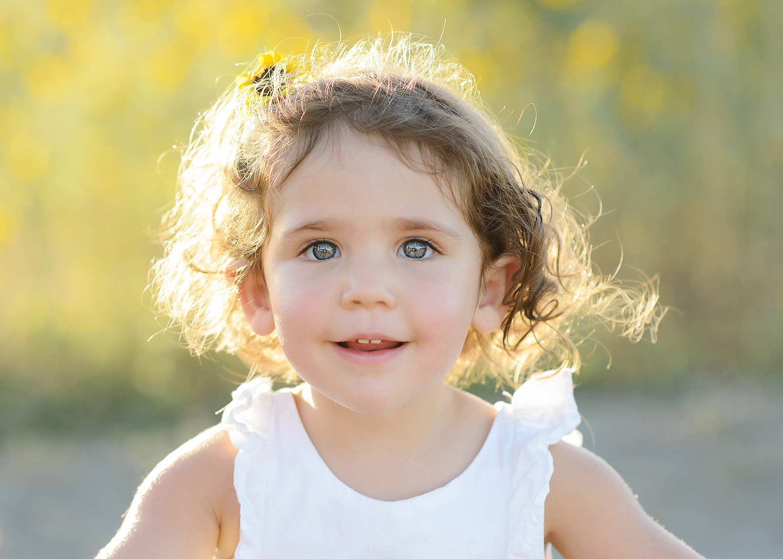 Baby Girl with Blue Eyes and Curly Hair in Natural Light