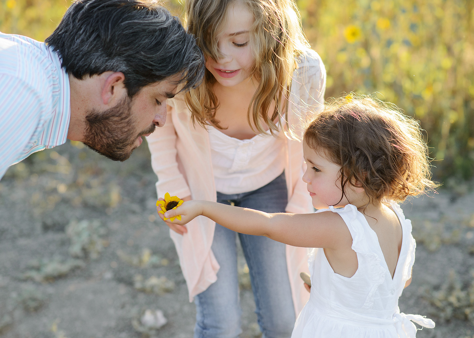 Dad and Daughters Smelling the Yellow Wildflowers