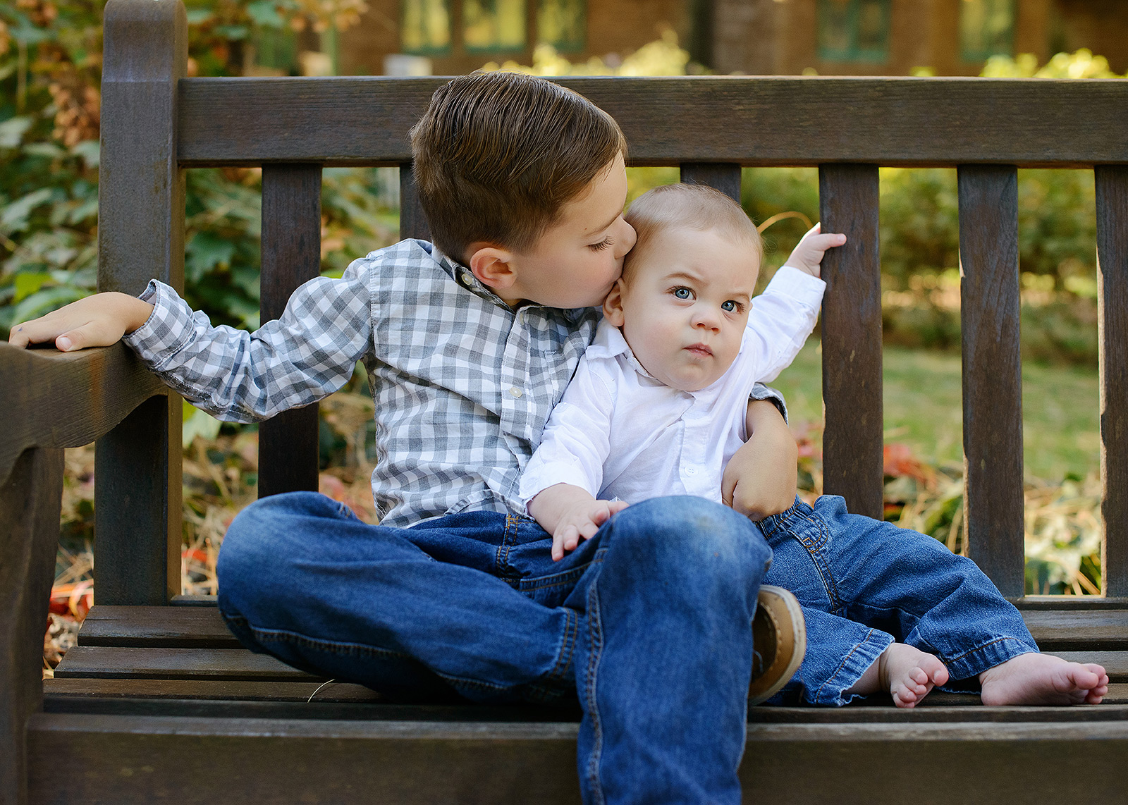 Brothers kissing on bench outdoors at Empire Mine