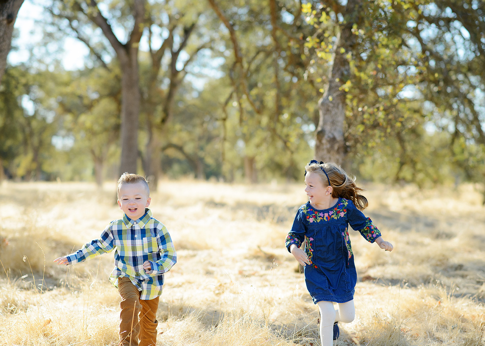 Brother and Sister Running Through Yellow Grass Field