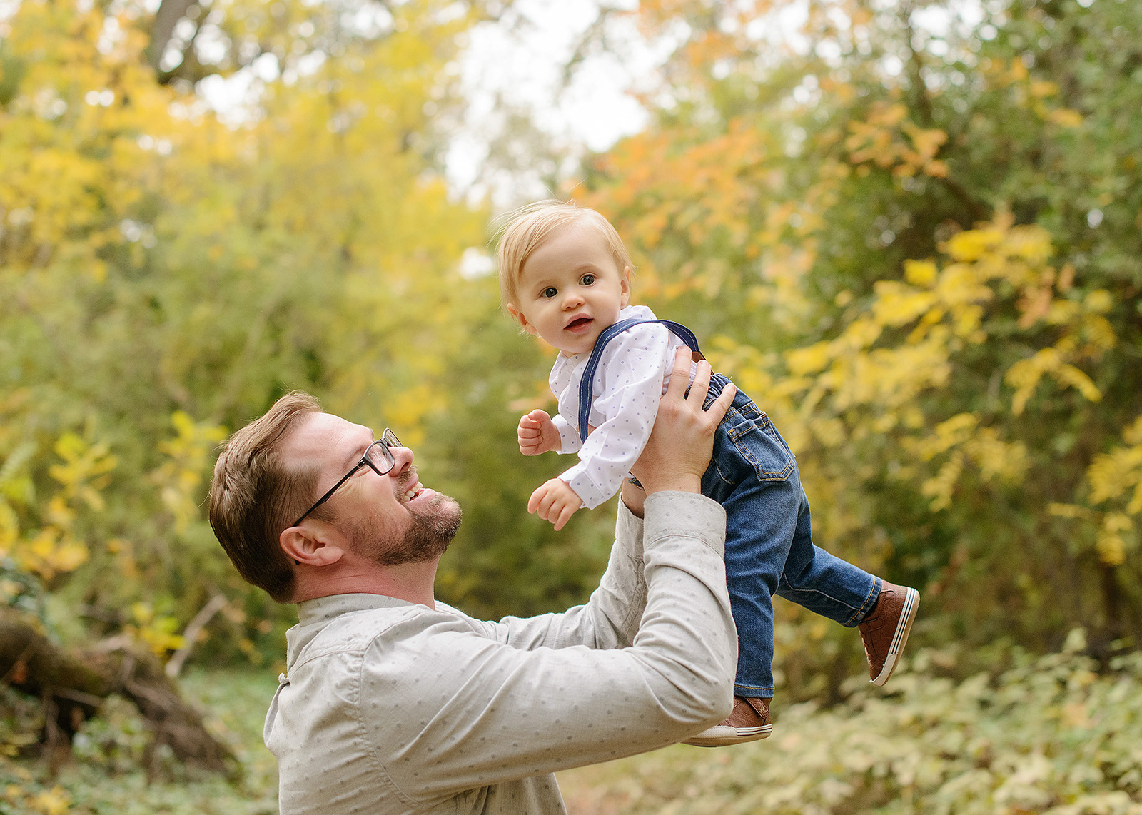 Father Lifting Baby Boy in Air Against Tree Foliage