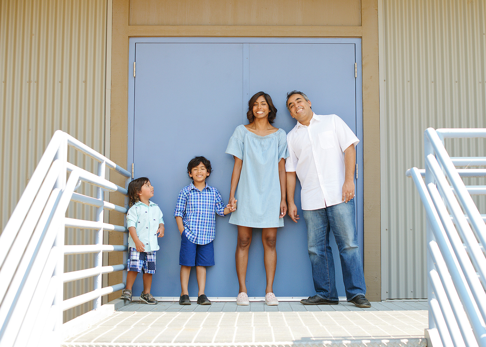 Family portrait in front of baby blue door stairway at Folsom Powerhouse
