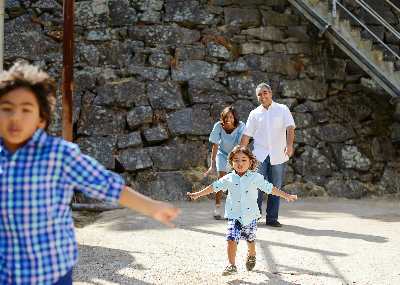 Boys running from mom and dad with stone background at Folsom Powerhouse