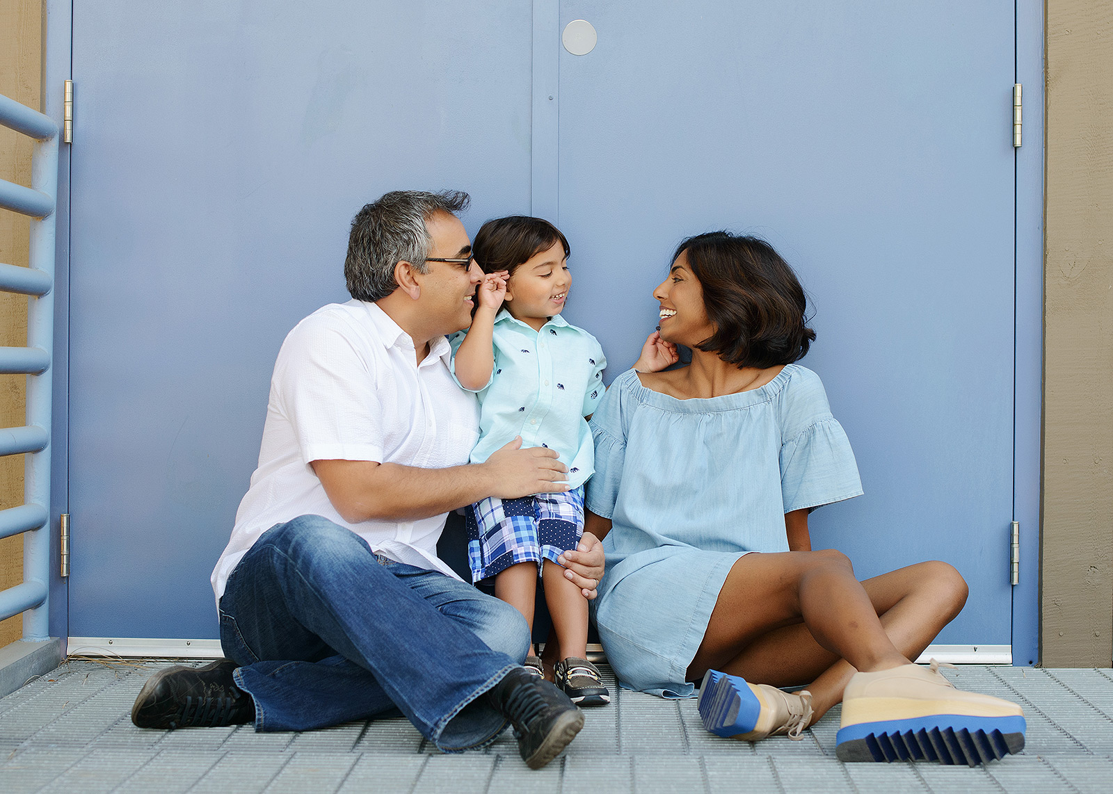 Dad, mom and son smile at each other in front of baby blue door at Folsom Powerhouse