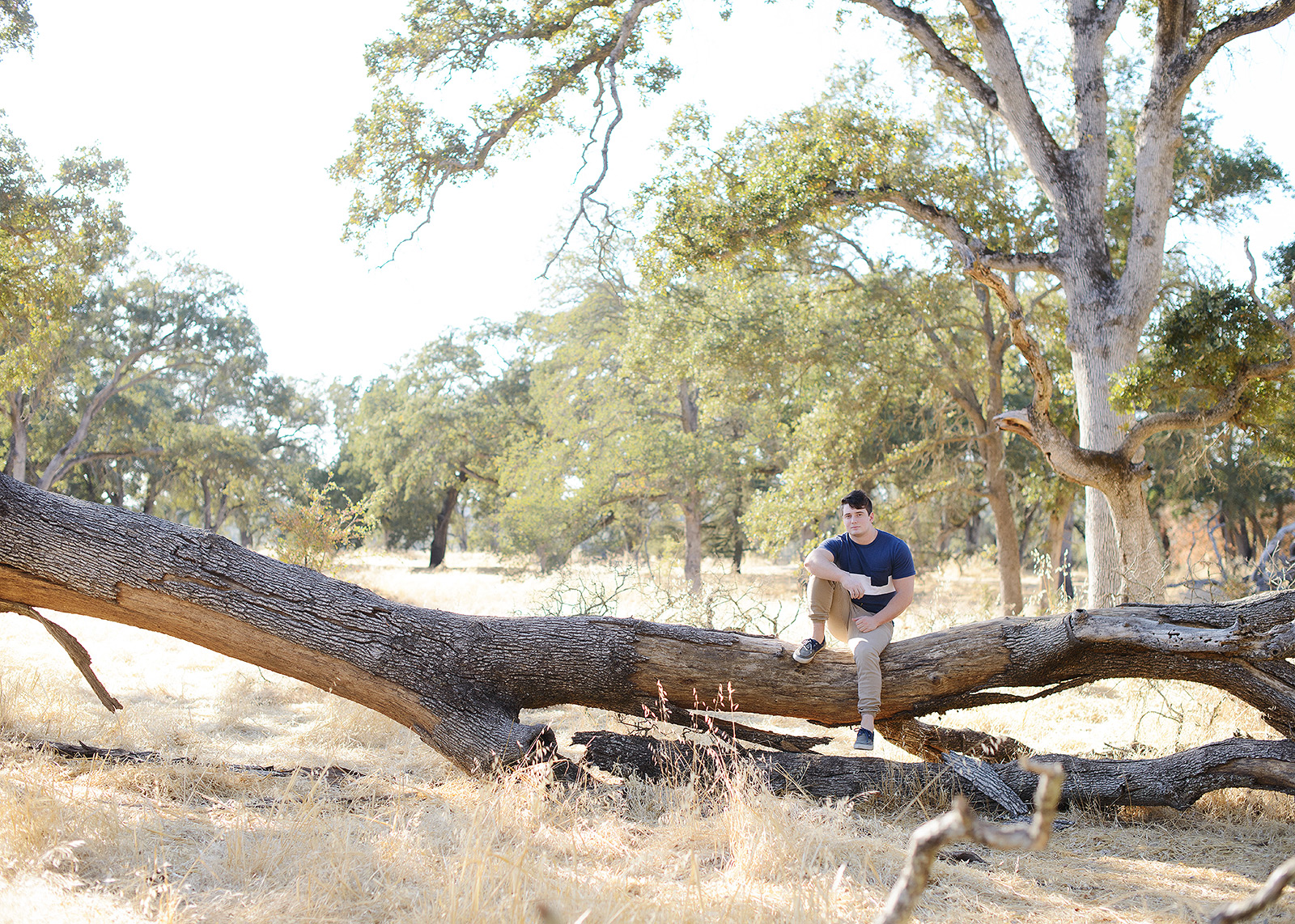 Male teenager sitting on fallen log in Folsom