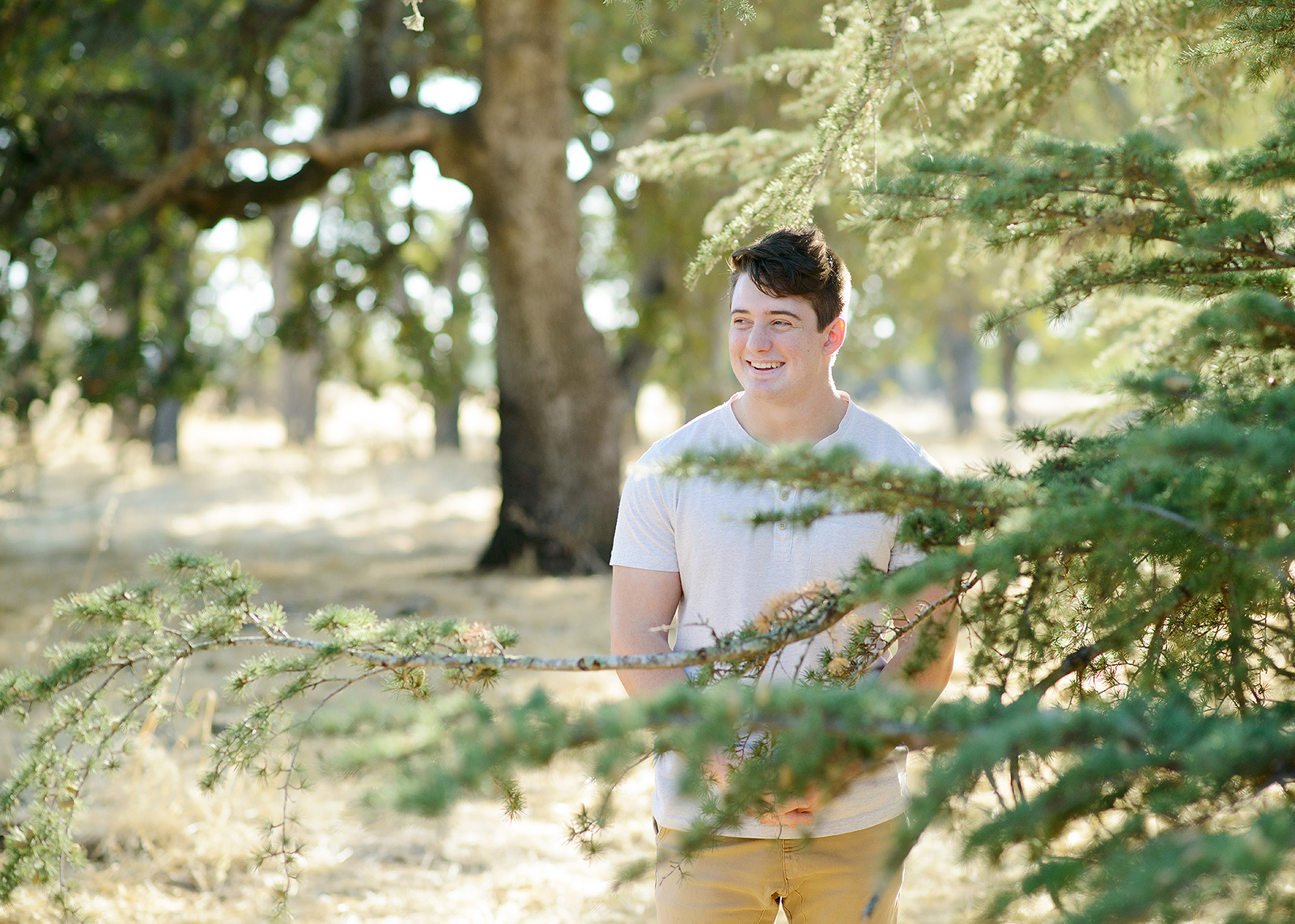 Teenage male smiling in between trees in Folsom