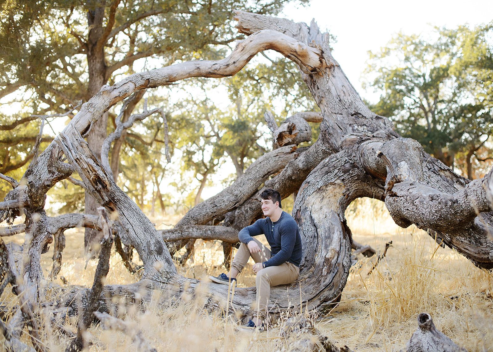 Male teen sitting on fallen tree and yellow grass in Folsom
