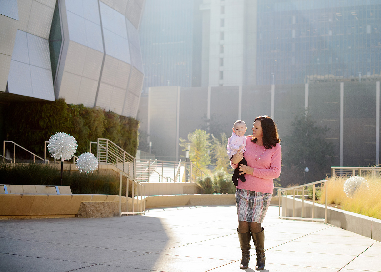 Mom Carrying Baby Boy in front of Golden 1 Center in Natural Light