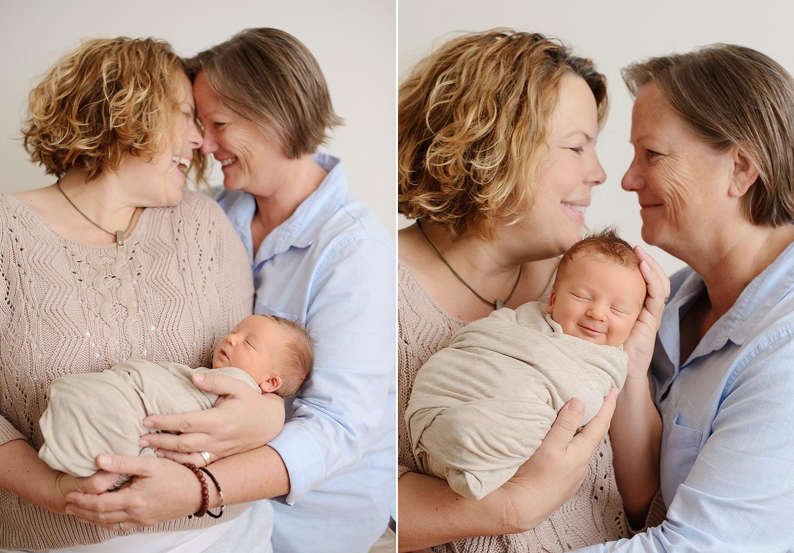 Moms cuddling newborn baby boy and smiling