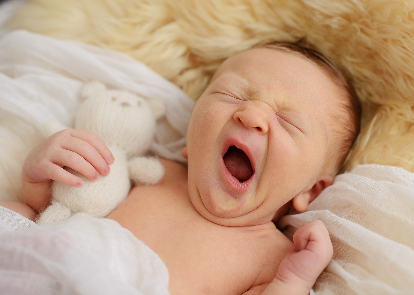 Newborn baby boy yawning on fur throw