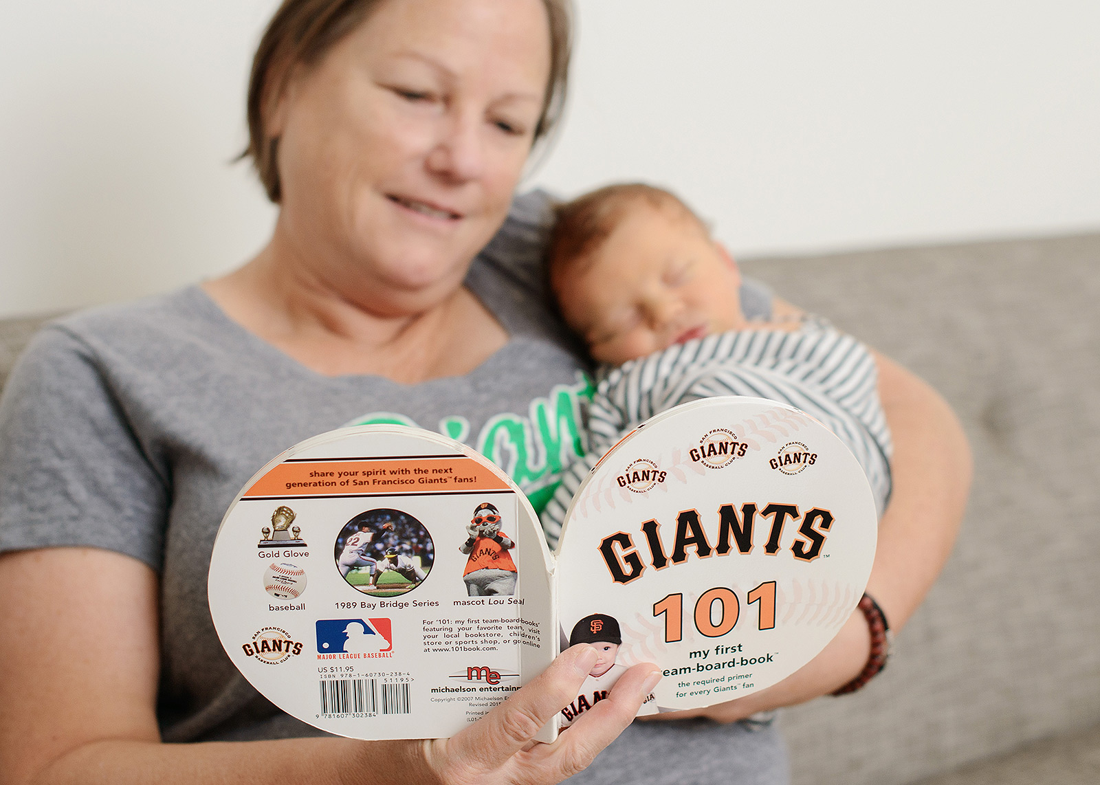 Mom reading San Francisco Giants book to newborn baby boy